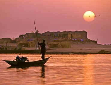Man on a boat at sunset on the Bani River in Mali.