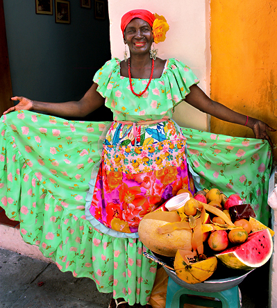 A woman in a bright, traditional dress, welcomes visitors to Cartagena, Colombia, with a basket of fruit.