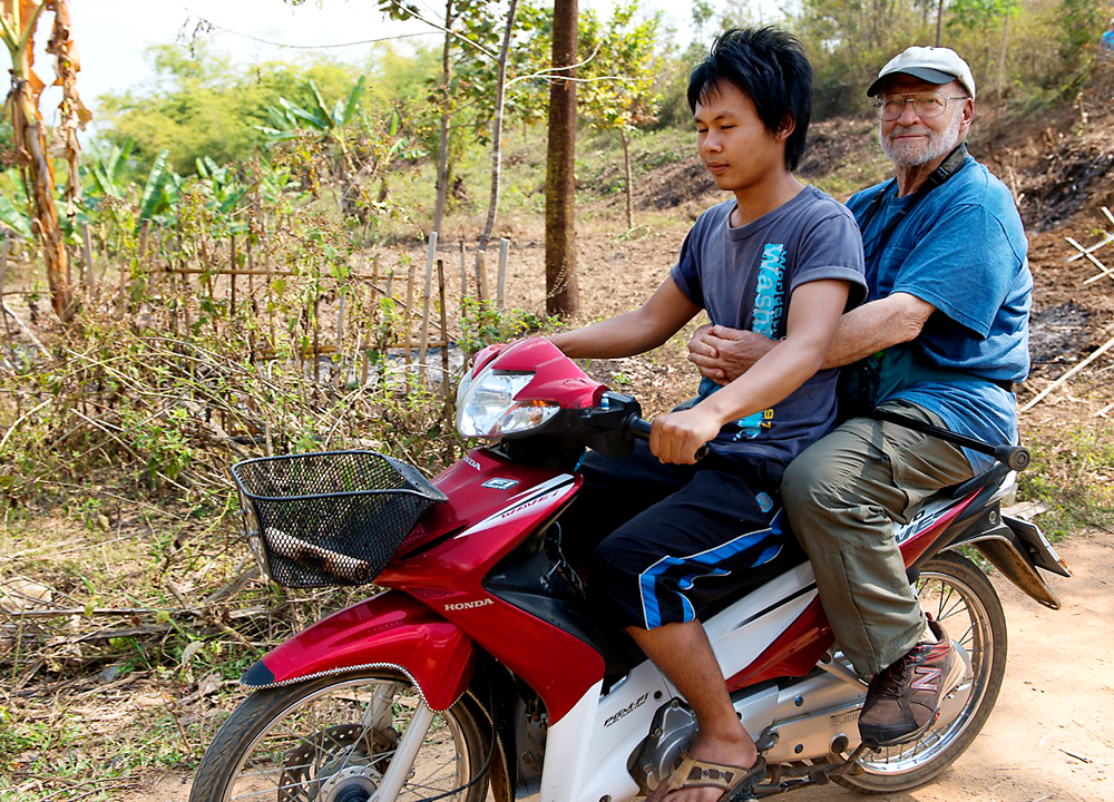 Photo of older traveler on the back of a moped in Burma.