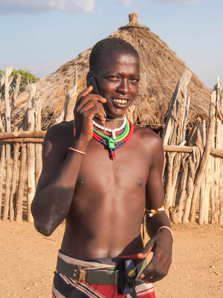 Hamar man with cell phone in from of hut